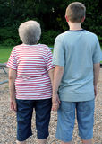 Generation Portrait 3. Grandmother and teenage grandson holding hands, with backs to camera royalty free stock photos