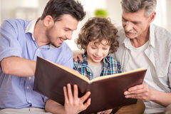 Generation. Portrait. Grandfather, father and son sitting and reading a book on sofa stock photo