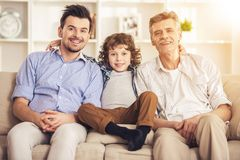 Generation portrait. Grandfather, father and son sitting on sofa.  Royalty Free Stock Photography