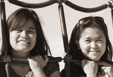 Generational Friendship. Two friends, a teenager and a mature mid-30s posing at a playground equipment with big smiles on their faces.  A concept of friendship Stock Photo