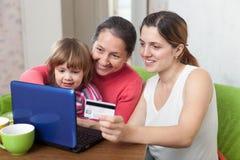 Generationen der dreiköpfigen Familie, die mit Kreditkarte in Internet-St. zahlen Stockbild