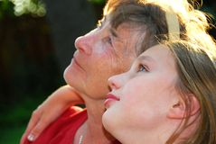 Generations. Portrait of a grandmother and granddaughter looking up with hope Stock Image