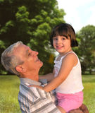 Generations. Grandfather playing with his little grand-daughter in a park Stock Photos