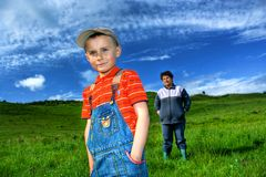 Generations. Boy with his grandmother on a meadow under blue sky Stock Photo