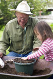 Generations. A young child is helping her Grandfather in the garden Royalty Free Stock Images