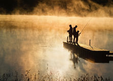 Generations. Early morning fishing in autumn on a lake as the mist rises from the water Royalty Free Stock Photo