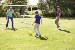 Generations-Familie des Manndrei, die zusammen Fußball spielt Stockbild
