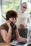 Generations gap. Mature woman talking on the phone, her mother listening behind Royalty Free Stock Image