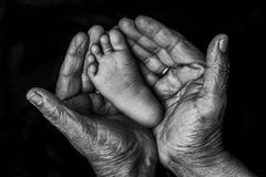 Indian hands and baby feet Stock Photo