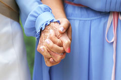Generations Holding Hands. Bride and grandmother hold hands on wedding day Royalty Free Stock Image