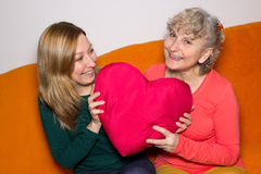 Generations together. Mother and daughter holding a heart in her hands Royalty Free Stock Image