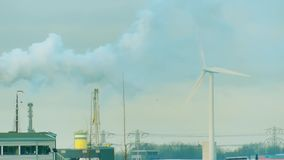 Generatore eolico e fumo giranti sopra la zona industriale Concetti puliti e sporchi di produzione di energia Fotografie Stock