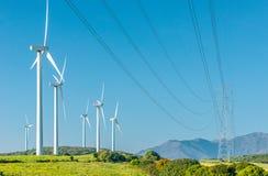 Generatore eolico e linee ad alta tensione in un campo Fotografia Stock Libera da Diritti