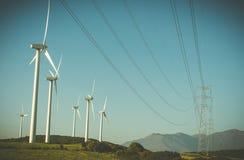 Generatore eolico e linee ad alta tensione in un campo Fotografia Stock