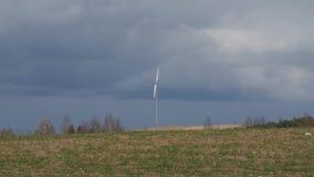 Generatore eolico nel campo verde con le nuvole scure in primavera archivi video