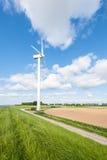 Generatore eolico sull'orlo di un campo arato Fotografia Stock