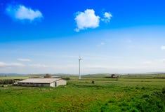 Generatore eolico vicino ad un'azienda agricola in una valle con cielo blu Fotografie Stock