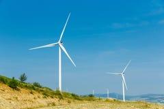 Generatori eolici che stanno sull'i talloni fra i campi Immagini Stock Libere da Diritti