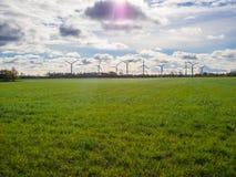 Generatori eolici che stanno sull'orizzonte con erba verde in priorità alta e cielo drammatico, autunno, Schlesvig-Holstein, Germ Immagine Stock