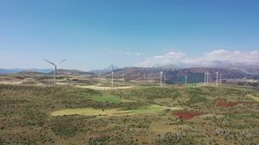 Generatori eolici con un trattore agricolo sul campo Trattore che lavora i campi polverosi vicino alla base dei generatori eolici archivi video