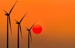 Generatori eolici della siluetta che generano elettricità Fotografie Stock