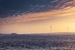 Generatori eolici durante l'orario invernale sul tramonto Fotografia Stock