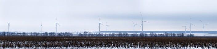 Generatori eolici giranti nella distanza in un campo nevoso Immagini Stock Libere da Diritti