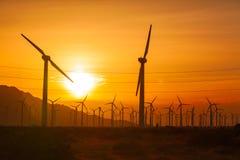 Generatori eolici profilati sopra il cielo drammatico di tramonto Immagini Stock Libere da Diritti