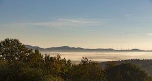 Generatori eolici rurali della collina della foresta degli alberi di mattina della foschia della nebbia del paesaggio immagine stock