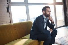 Generazione delle idee Giovane l'uomo d'affari sicuro e bello sta pensando all'affare mentre si sedeva sul sofà nel suo immagini stock libere da diritti