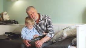 Generazione nonno e nipote con il contenitore di regalo che si siede sullo strato a casa stock footage