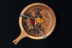 Genere differente di spezie: paprica, granelli di pepe in piatto di legno immagini stock