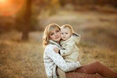 Generi abbracciare il suo bambino durante la passeggiata nel parco immagine stock