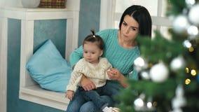 Generi abbracciare sua figlia che si siede sul davanzale vicino all'albero di Natale archivi video