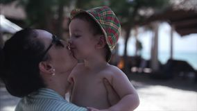 Generi abbracciare suo figlio sulla famiglia felice della costa, lungo il litorale video d archivio