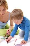 Generi aiutano il suo figlio con l'illustrazione. Fotografia Stock