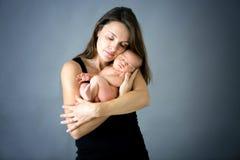 Generi baciare ed abbracciare il figlio neonato a fondo grigio, tende Immagine Stock