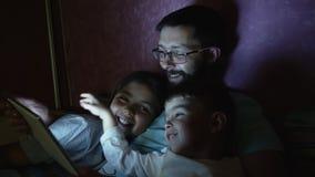 Generi con i piccoli bambini che praticano il surfing sul computer della compressa prima del sonno video d archivio