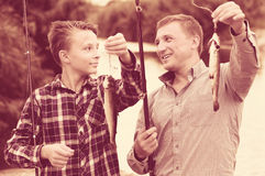 Generi con il figlio che esamina il pesce sul gancio Fotografie Stock Libere da Diritti
