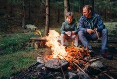 Generi con il fuoco di accampamento vicino caldo del figlio, beva il tè ed abbia conversat immagini stock libere da diritti