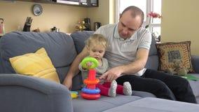 Generi con il gioco della figlia del bambino con la piramide variopinta dei cerchi di istruzione sul sofà archivi video
