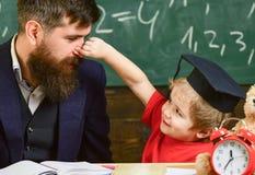 Generi con la barba, insegnante insegna al figlio, ragazzino, mentre bambino che pizzica il suo naso Insegnante ed allievo in toc Fotografia Stock Libera da Diritti