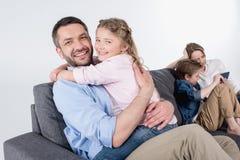 Generi con la figlia che abbraccia e che esamina la macchina fotografica mentre madre con il figlio Fotografia Stock