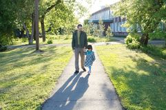 Generi con la figlia che cammina nel parco al giorno soleggiato papà con la bambina all'aperto Ritratto autentico della famiglia Immagini Stock Libere da Diritti