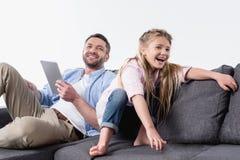 Generi con la figlia che si siede sul sofà con la compressa digitale Immagine Stock