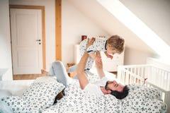 Generi con un ragazzo del bambino divertendosi nella camera da letto a casa all'ora di andare a letto fotografia stock