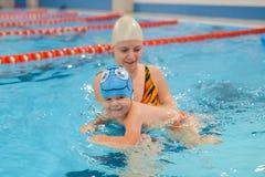 Generi dare al figlio una lezione di nuoto in stagno all'interno Immagini Stock