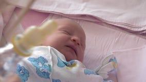 Generi dare la bottiglia con acqua al neonato sonnolento video d archivio