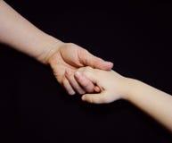 Le mani del figlio e della madre su fondo nero Immagine Stock