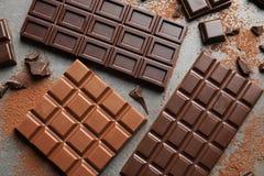 Generi differenti di cioccolato su fondo grigio immagine stock libera da diritti